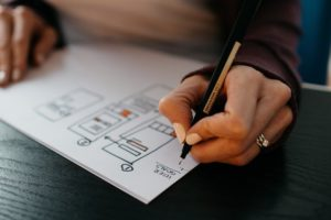 hand with pen drawing up user experience sitemap - Waypath