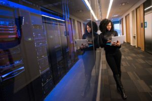 girl standing near server room holding laptop - WayPath Consulting - Microsoft Dynamics 365