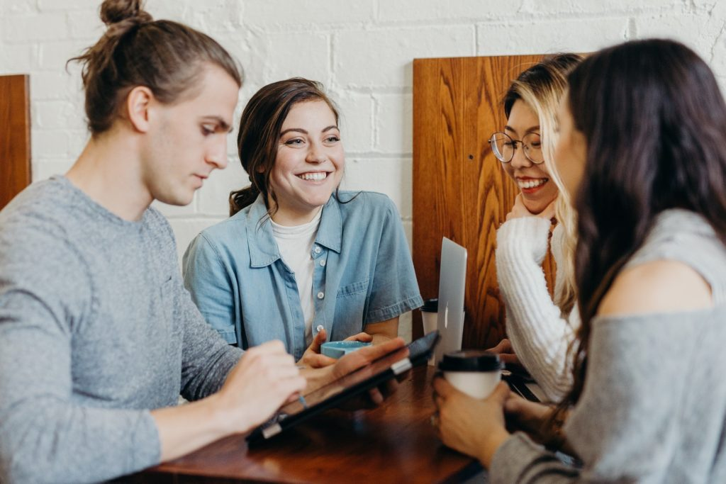 four people sitting around a table smiling | WayPath Consulting