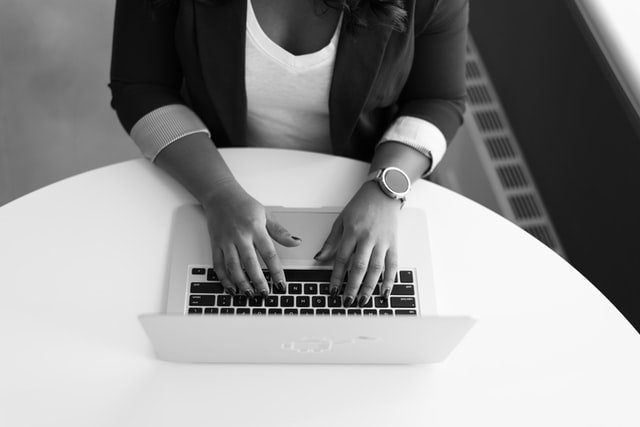 lady typing on laptop - blak white photo - Sitecore Problems Features