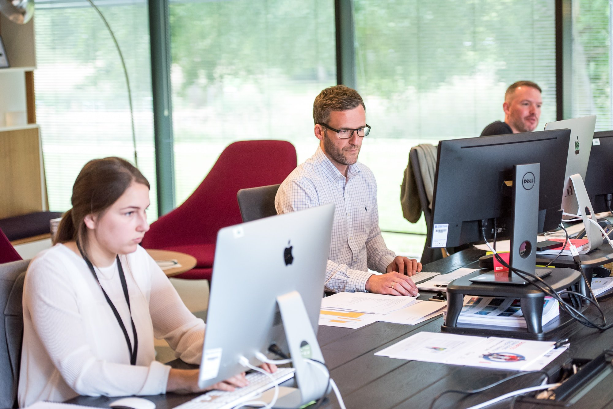 three staff members working at table with computers | WayPath Consulting