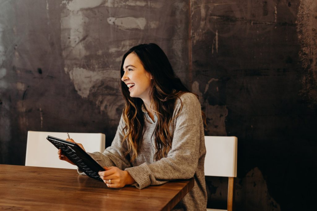 woman smiling while sitting at table holding tablet | WayPath Consulting